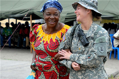U.S. Army Maj. Angie Allmer assists a Congo resident to the medical waiting area in Kinshasa