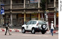 Two men throw stones at a UN car as they run after it in the streets of Kinshasa, Aug. 21, 2006<br /><br />
