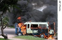A Congolese police van burns outside the smoldering supreme court building in Kinshasa, Tuesday, Nov. 21, 2006