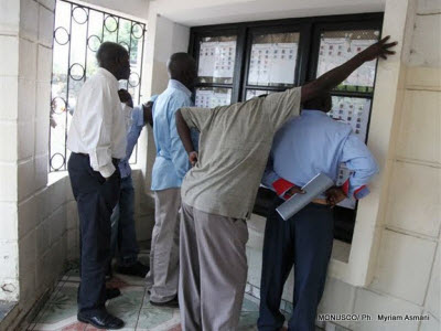 People look for their names on a voters' list at a polling center in Goma
